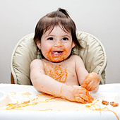 Happy baby having fun eating messy covered in Spaghetti Angel Hair Pasta red marinara tomato sauce. - Stock Image - C2600X