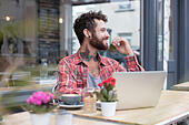 Young tattooed hipster using laptop outside cafe - Stock Image - H821HE
