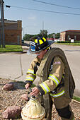 Female firefighter in rural volunteer fire department working with equipment. - Stock Image - EXHY43