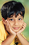 small young Indian boy face between both hands India   MR#152 - Stock Image - CE6DPT