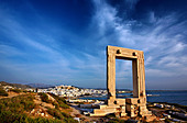 The Portara (temple of Apollo) and the Chora ('capital') of Naxos island in the background. Cyclades, Greece - Stock Image - CPK2WB