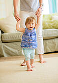 Mother assisting baby daughter (18-23 months) with her first steps - Stock Image - E7PAYP