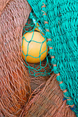 Red and green fishing nets and yellow float - Stock Image - A2YB39