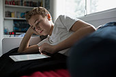 Boy using digital tablet on bed - Stock Image - FDP6E2