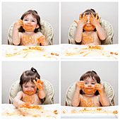 Happy baby having fun eating messy showing hands covered in Spaghetti Angel Hair Pasta red marinara tomato sauce. - Stock Image - C2603T