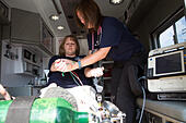Female paramedics working in the back of an ambulance. Rural volunteer US fire department. - Stock Image - EXGY12
