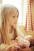 Close up of a girl carrying her sister - Stock Image - B50N87