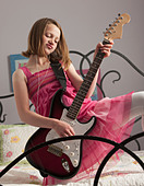 Young girls playing guitar on her bed - Stock Image - BNW53W