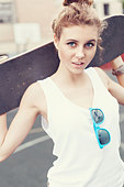 Young active woman in blue sunglasses standing with a skateboard in her hands in the daytime. Outdoors - Stock Image - D8J33H