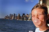 teenage girl looks out over the New York Manhattan skyline USA while blowing her bubblegum.  FULLY MODEL RELEASED/CONSENTED - Stock Image - BX8BNK