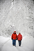 A couple in matching red winter coats walking in a Cotswold lane in snowy conditions UK - Stock Image - CEJEXA