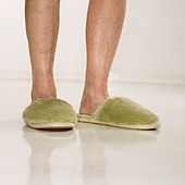 Caucasian senior female feet wearing green bedroom slippers - Stock Image - A8JD0Y