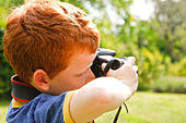 A Young boy, aged 7, using a digital SLR camera in a sunny garden. - Stock Image - CBH1FR