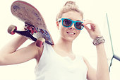 Young woman in blue sunglasses standing with a skateboard in her hands in the daytime. Outdoors - Stock Image - D8J342
