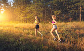 Young sporty girls running on a field near the trees at sunset in summer. Athlete running on the off road in the evening. Active woman. Sport and heal - Stock Image - HWGCXG