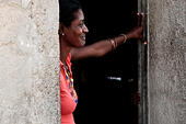 A woman stands in the doorway of her home. Cubans spend much time at their doorways and many activities take place on the doorstep and street, creating a sense of community with their neighbors. Home interiors clearly demonstrate the poverty, dimness and deficiencies so common in Cuban lives. - Stock Image - EJEMK2