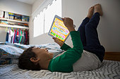 Boy feet up using digital tablet on bed - Stock Image - FDP59G