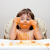 Happy baby having fun eating messy covered in Spaghetti holding Angel Hair Pasta red marinara tomato sauce. - Stock Image - C2609B