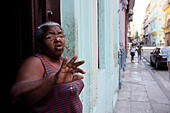 A woman stands at her doorway conversing with a friend in Havana, Cuba. Cubans spend much time at their doorways and many activities take place on the doorstep and street, creating a sense of community with their neighbors. Home interiors clearly demonstrate the poverty, dimness and deficiencies so common in Cuban lives. - Stock Image - EJETEA