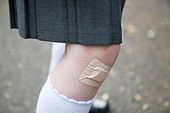 Schoolgirl's knee with a sticking plaster over a cut. - Stock Image - CNH2M1