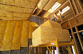 R38 Fiberglass Insulation being installed roof in new loft style home under construction - Stock Image - A26TKY
