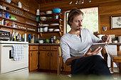 Man using digital tablet at cabin kitchen table - Stock Image - F5CKTT