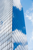 Blue cloudy sky reflected in windows of modern skyscraper - Stock Image - D9DHJ1