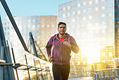 athlete with earphones running in the city - Stock Image - H7MHB7