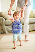 Mother assisting baby daughter (18-23 months) with her first steps - Stock Image - E7PAYT