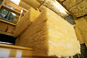 R38 Fiberglass Insulation being installed in roof in new loft style home under construction - Stock Image - A26TMH