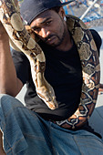 Man with pet python on the boardwalk at Coney Island - Stock Image - A5KWT5