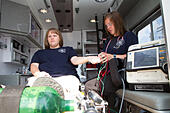 Female paramedics working in the back of an ambulance. Rural volunteer US fire department. - Stock Image - EXGXC1