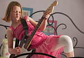 Young girls playing guitar on her bed - Stock Image - BNW53N