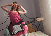 Young girls playing guitar on her bed - Stock Image - BNW548