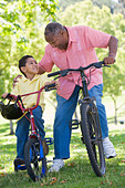 Grandfather and grandson on bikes outdoors smiling - Stock Image - B3K7A5