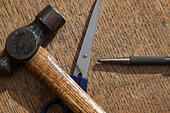 Ball pein hammer, scissors and a centre/centrer punch on a wooden surface - Stock Image - HG7MWP