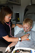 Female paramedic assisting young male patient in back of ambulance. - Stock Image - EXGWGM