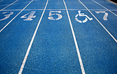 Handicap wheelchair icon superimposed on top of running track. - Stock Image - C4N87R