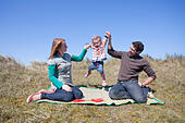 A young family having fun on the sand dunes at Horsey Beach on the Norfolk coast. - Stock Image - DYDCRA