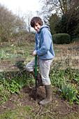 Model released teenage boy digging hole in garden - Stock Image - BK7FWT