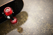Skateboard in puddle - Stock Image - B22TXF