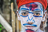 Silchar, Assam - circa April 2012: Young big-eyed boy with white powder and blue and red ornaments on his face wears red headband in Silchar, Assam. D - Stock Image - HGFCHP