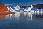 Cruising between the icebergs at Røde Ø, Scoresbysund, Greenland - Stock Image - CBY337