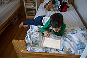 Boy drawing with digital tablet on bed - Stock Image - FDP58H