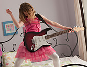 Young girls playing guitar on her bed - Stock Image - BNW53G