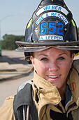 Female firefighter in rural volunteer fire department working with equipment. - Stock Image - EXJ16R