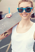 Young happy woman in blue sunglasses standing on the playground with a skateboard in her hands in the daytime. Outdoors - Stock Image - D8J33T