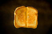 A Grilled Cheese Sandwich cut in half pulling the cheese on a wood table - Stock Image - C088J3