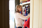 Woman In Bedroom Looking At Clothes In Wardrobe - Stock Image - G2TNK7