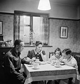 Member of the Home Guard eating tea with his family prior to going on duty, 1942. D10118 - Stock Image - D95RX0